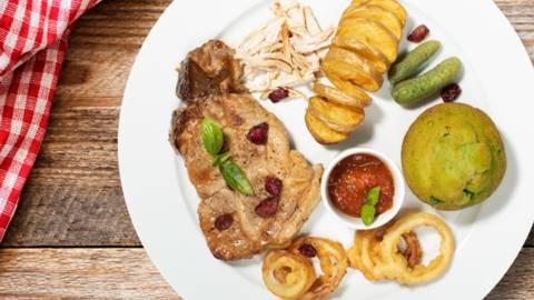 Ameriški svinjski kotleti z bučnim biskvitom, natrganim puranjim mesom, hrustljavim spiralnim krompirčkom, čebulnimi obročki, ameriško omako in bru...