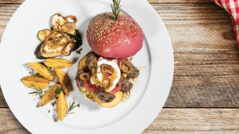Sočni pisani hamburger po ameriško s čevapčiči in karamelizirano čebulo v družbi zeliščnega krompirja in bučk