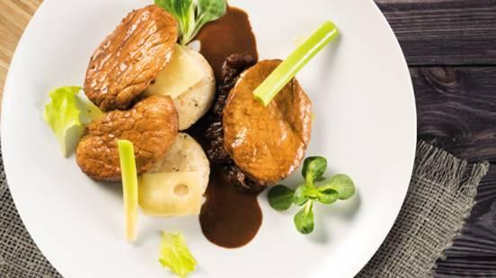Dušeni svinjski zrezki v raguju iz rozin z kruhovimi cmoki in omako iz kumine
