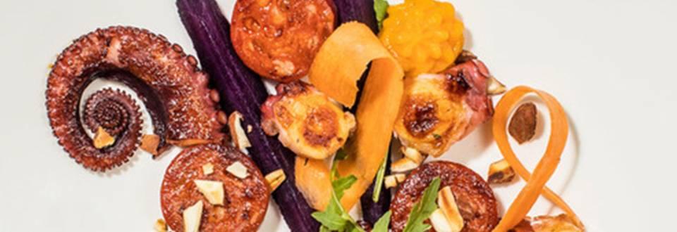 Hobotnica s pikantno klobaso chorizo na oranžnem korenjevem pireju z rezinami mariniranega vijoličastega korenja in trakovi mladega korenčka
