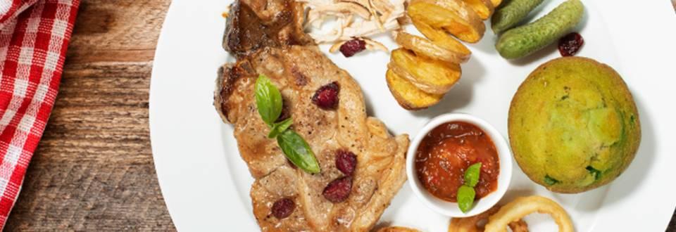 Ameriški svinjski kotleti z bučnim biskvitom, natrganim puranjim mesom, hrustljavim spiralnim krompirčkom, čebulnimi obročki, ameriško omako in brusnicami